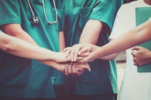 Doctor and Nurses team stacking hands - Gifted Healthcare